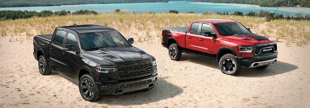 Two 2020 Ram 1500 trucks parked on sandy beach red and black