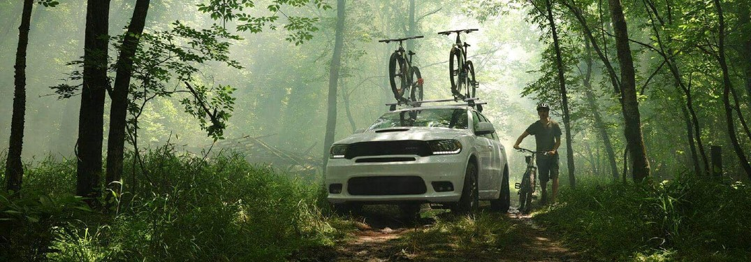 2020 Dodge Durango White in green forest carrying bikes with biker on side