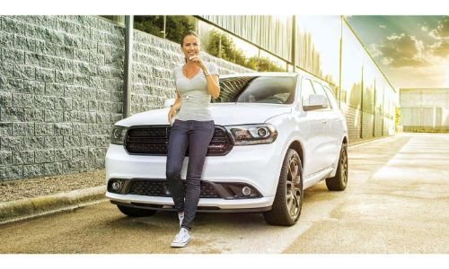 2020 Dodge Durango White woman leaning on front grille white brick building