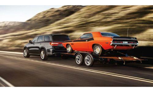 2020 Dodge Durango towing a Dodge Challenger orange with black stripe