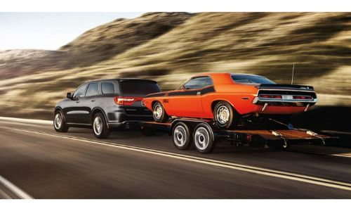 2020 Dodge Durango towing a Dodge Challenger orange with black stripe
