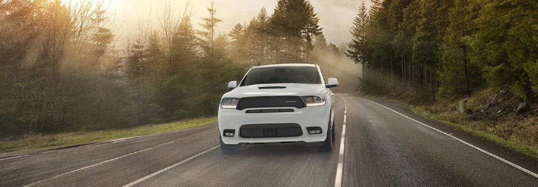 2020 Dodge Durango white driving through forested road with sunbeams in mist