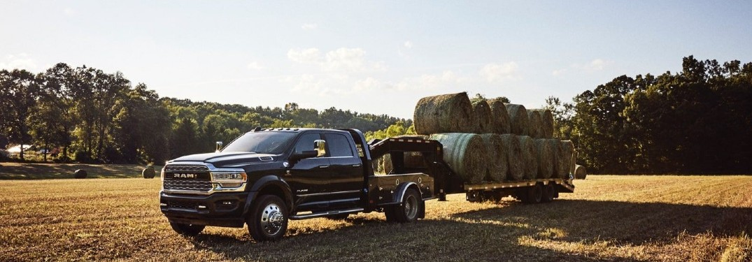 2020 Ram 5500 black parked in farmland pulling trailer of hay bales