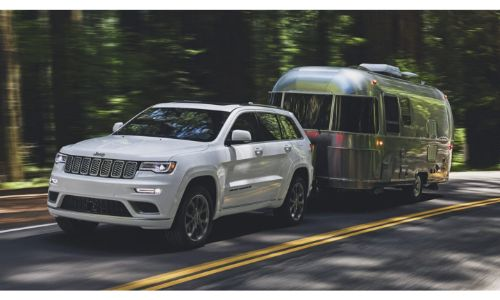 2020 Jeep Grand Cherokee towing a silver trailer through forest road