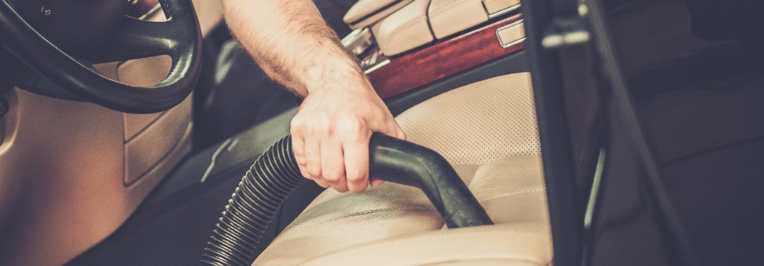 stock photo of hand holding vacuum cleaning leather car seat