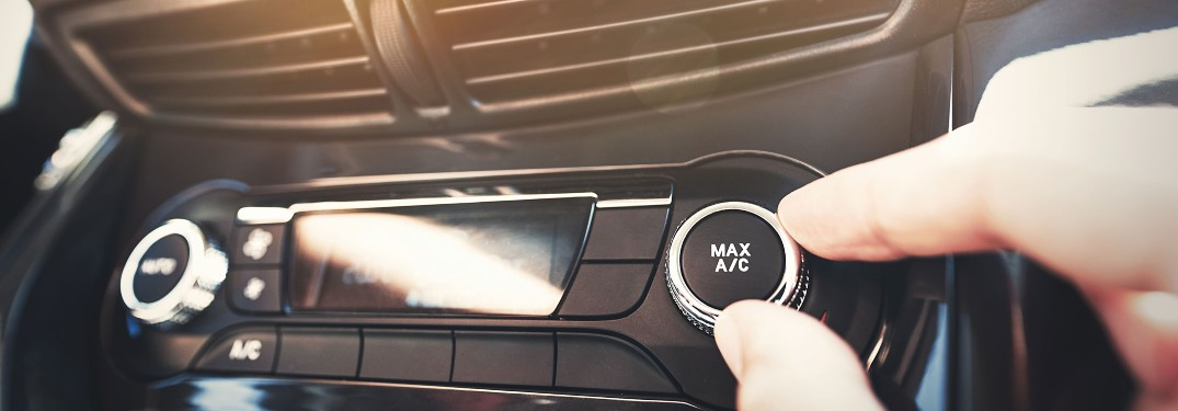 stock photo of hand turning A_C knob under air vents