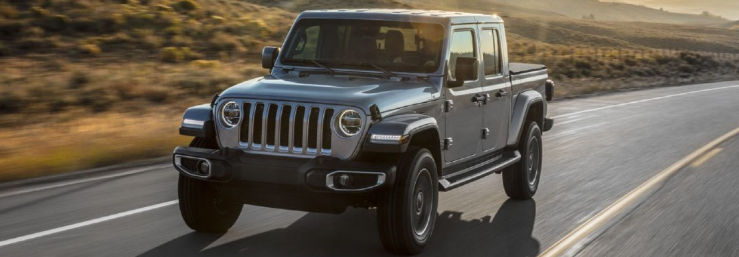 2020 Jeep Gladiator grey driving down curved road sunset in background