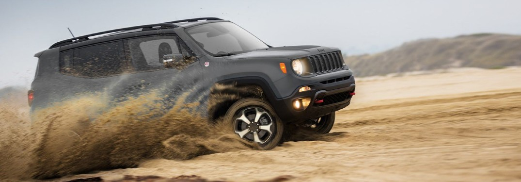 2020 Jeep Renegade gray driving through sand with mountains in background