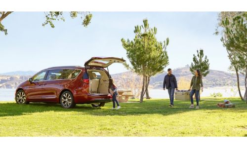 2020 Chrysler Pacifica red paint parked in park back open grass lake hills and sky_o