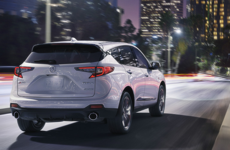 2019 Acura RDX rear quarter view driving into city at night