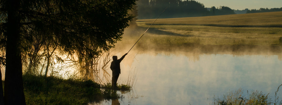 Fisherman casting into lake at sundown