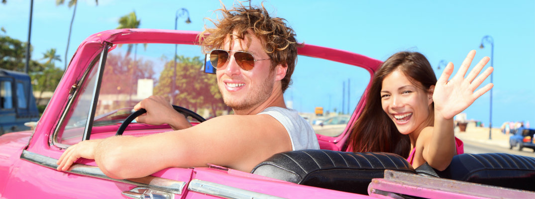 Man and woman facing camera and sitting in pink convertible