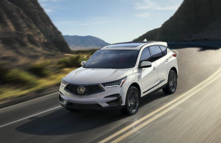 White 2019 Acura RDX driving on mountainous road