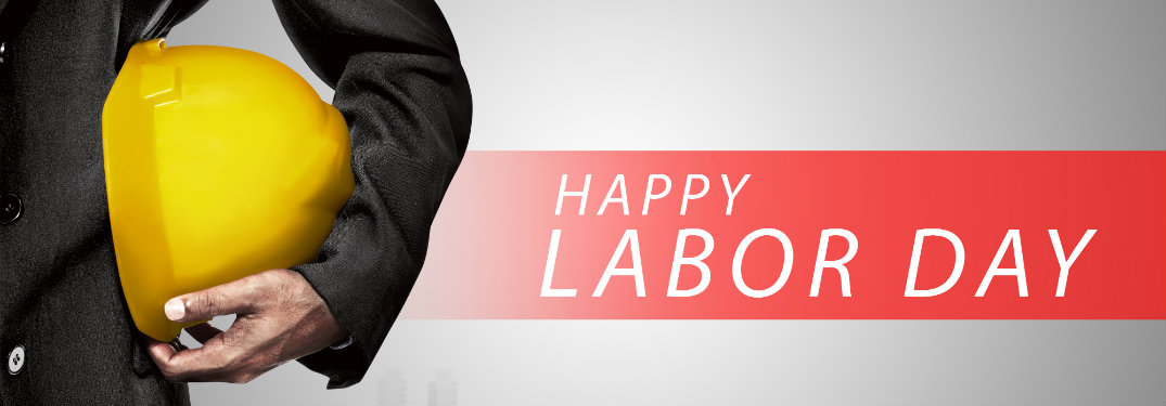 """Worker with hard hat next to banner stating """"Happy Labor Day"""""""