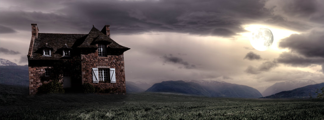 Haunted House with ominous moon glowing through night sky