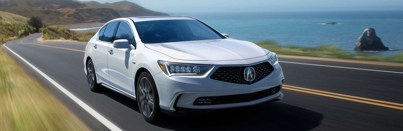 White Acura RLX driving on road beside ocean