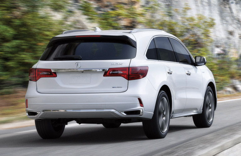 Rear view of white 2019 Acura MDX driving on wooded road