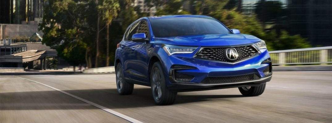 Blue 2019 Acura RDX driving on empty tree-lined road
