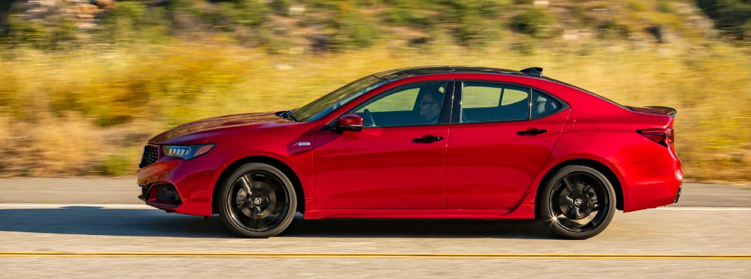 2020 Acura TLX PMC edition red driving to the left on asphalt with dried grasses in background