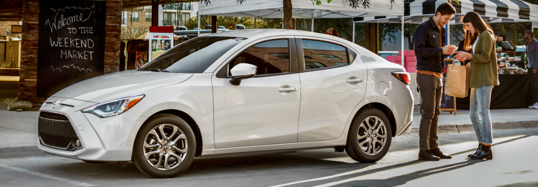 Man and a Woman Standing next to a White 2019 Toyota Yaris Sedan