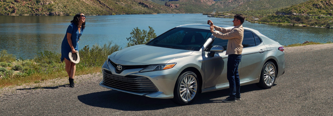 Man Taking a Photo of a Woman Next to a Silver 2018 Toyota Camry