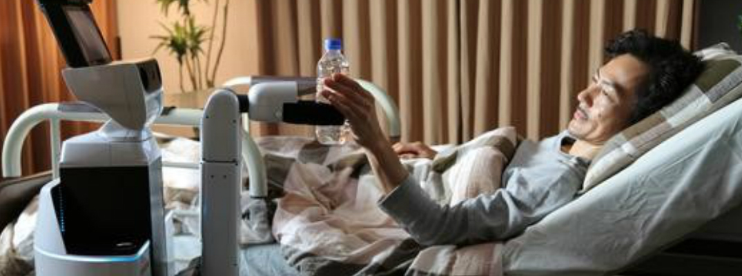 Man in a Hospital Bed Helped by a Robot