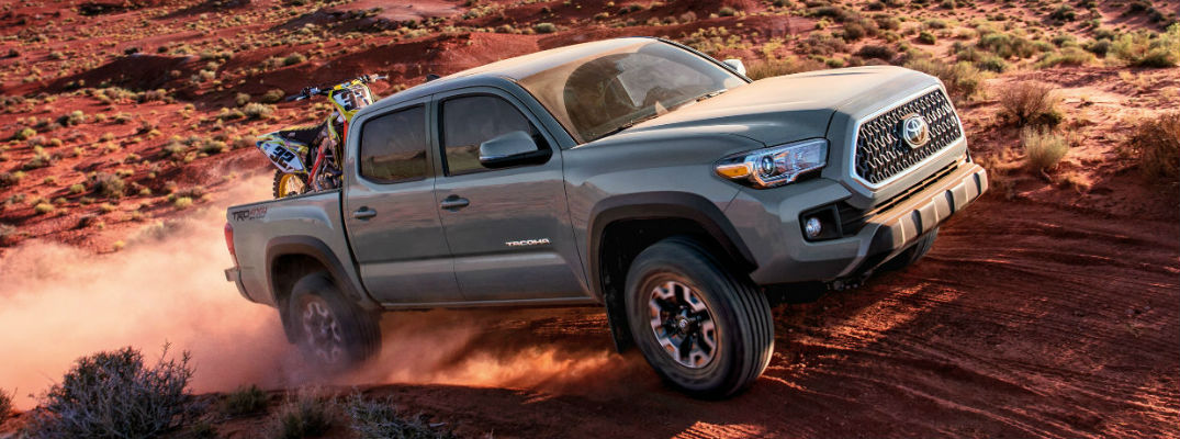 A photo of a Toyota Tacoma crossing the desert with dirt bikes the back