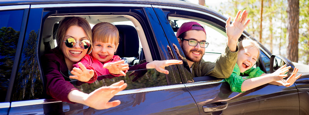 A stock photo of a family in their car ready to leave on a trip.