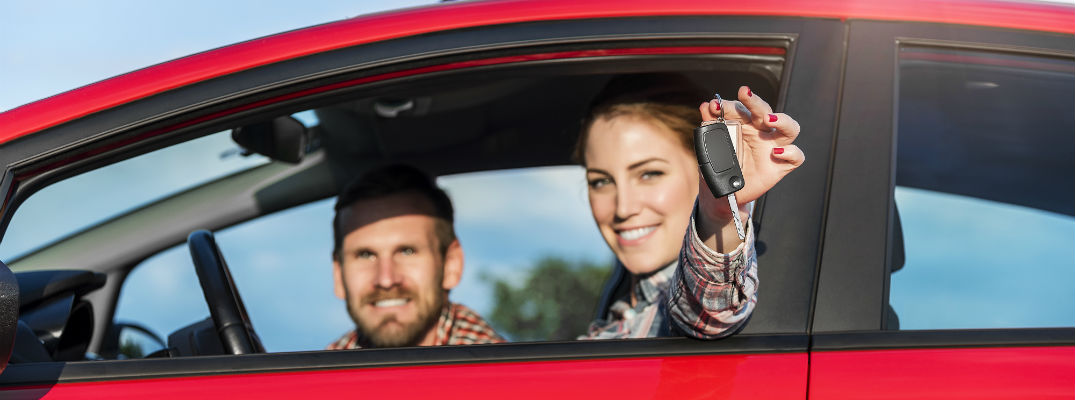 A stock photo of a young couple sitting in a car holding a set of keys.
