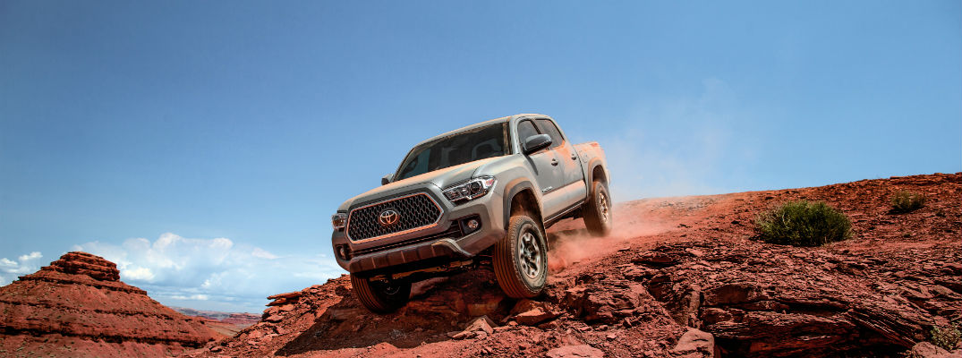 A photo of a 2018 Toyota Tacoma coming over a hill in the desert.