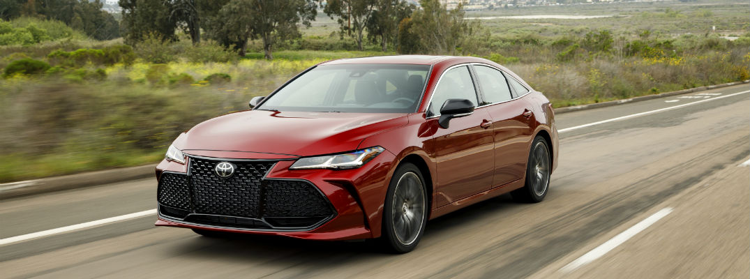 A front left quarter photo of the 2019 Toyota Avalon driving on the road.