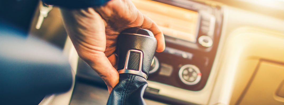 A stock photo of a person shifting gears with a manual transmission.