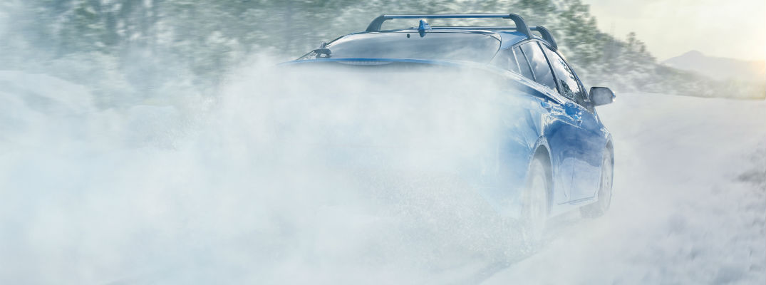 A rear photo of the 2019 Toyota Prius driving over a snow-covered road.