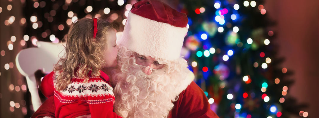 A stock photo of a child speaking to Santa Claus.