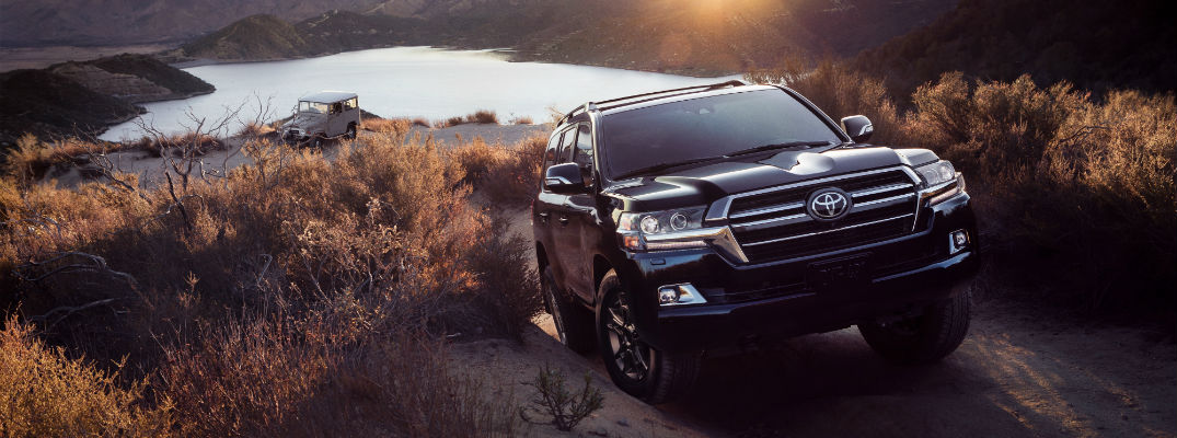 A photo of the 2020 Toyota Land Cruiser Heritage Edition climbing a hill with a first-generation model in the background.