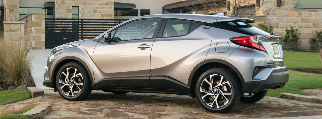 A left profile photo of the 2019 Toyota C-HR parked in front of a house.