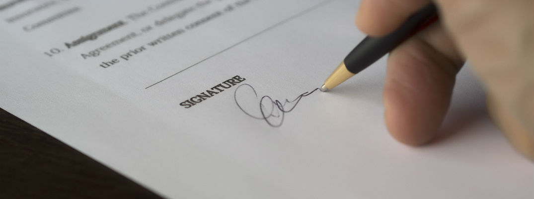 A stock photo of someone signing some kind of paper work.