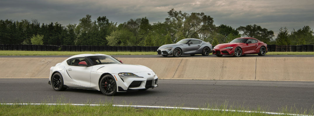 A photo of three 2020 Toyota Supra models parked on the bank of a race track.