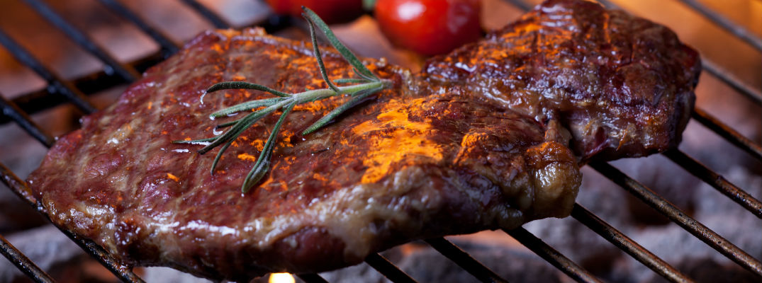 A stock photo of a steak being cooked on the grill.