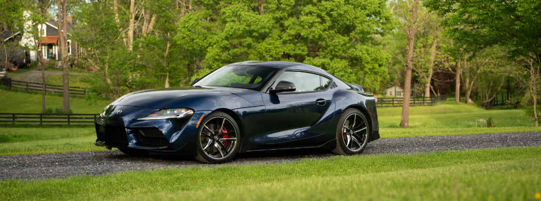 A left profile photo of the 2020 Toyota Supra parked by a field.