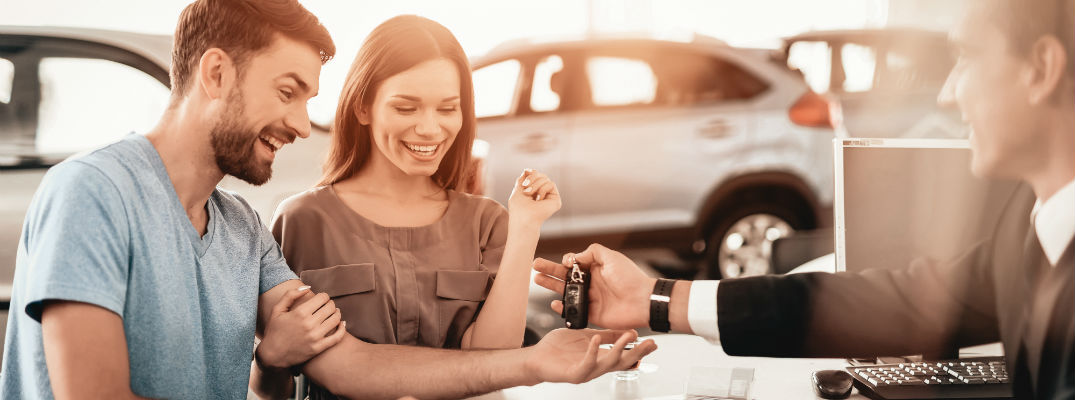 A stock photo of people picking up their keys for a new car.