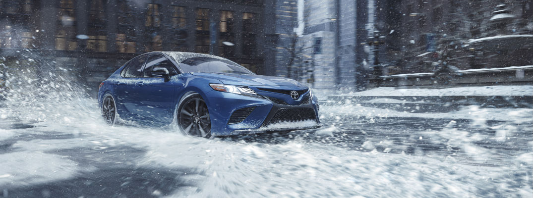 A photo of the 2020 Toyota Camry driving in a city during winter.