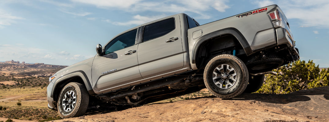 A photo of the 2020 Toyota Tacoma driving over uneven ground in the desert.