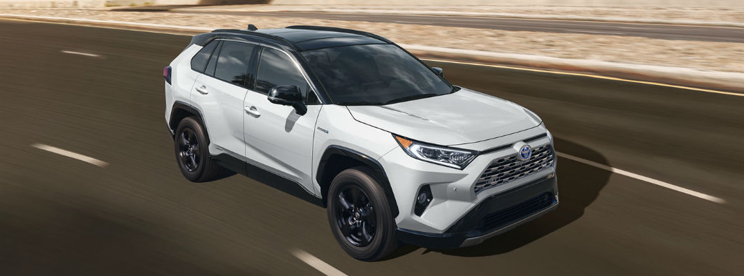 A front right quarter photo of the 2020 Toyota RAV4 Hybrid in motion on the road.