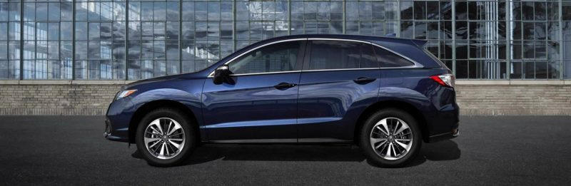 A blue 2018 Acura RDX sits in profile in a city.