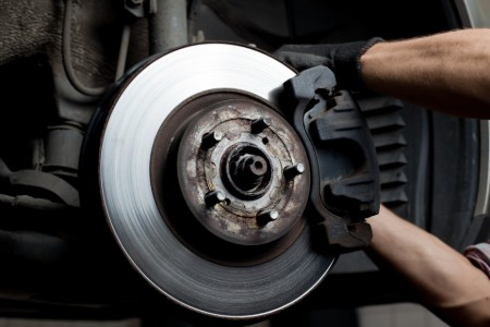Close up of a brake in a car with a mechanic replacing the brake pads