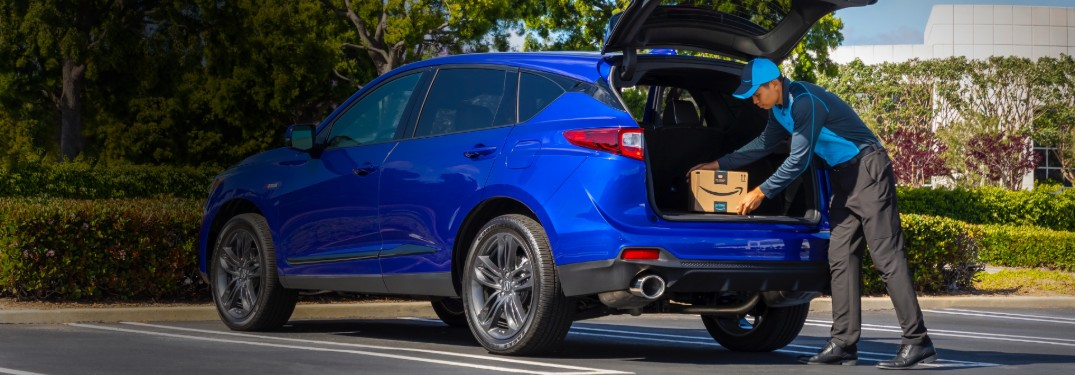 Rear passenger view of a blue Acura RDX with the trunk open and an Amazon delivery driver placing a package inside