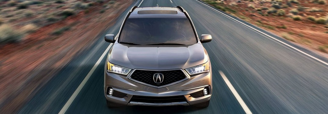 Front angle of a grey 2020 Acura MDX driving down a road