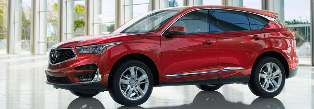 Front driver angle of a 2020 Acura RDX in Performance Red color parked inside a building