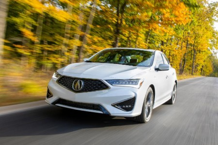 Front driver angle of a white 2020 Acura ILX driving down a road with yellow trees in the background